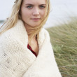 Young Woman Standing In Sand Dunes Wrapped In Blanket - Stock Photo