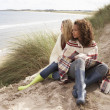 Two Teenage Girls Sitting In Sand Dunes Wrapped In Blanket — Stock Photo