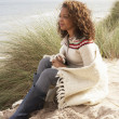 Young Woman Sitting In Sand Dunes Wrapped In Blanket — Stock Photo