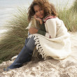 Young Woman Sitting In Sand Dunes Wrapped In Blanket - Foto Stock