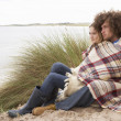 Teenage Couple Sitting In Sand Dunes Wrapped In Blanket - 图库照片