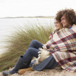 Teenage Couple Sitting In Sand Dunes Wrapped In Blanket — Stock Photo