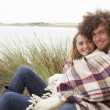 Stock Photo: Teenage Couple Sitting In Sand Dunes Wrapped In Blanket