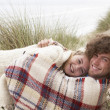 Teenage Couple Sitting In Sand Dunes Wrapped In Blanket - Foto Stock