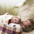 Teenage Couple Sitting In Sand Dunes Wrapped In Blanket - Foto de Stock