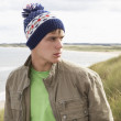 Teenage Boy Standing In Sand Dunes Wearing Woolly Hat — Stock Photo