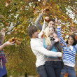 Stock Photo: Group Of Teenage Friends Throwing Leaves In Autumn Landscape