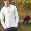 Teenage Boy Standing In Autumn Park With Female Figure On Bench — Foto Stock