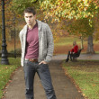 Teenage Boy Standing In Autumn Park With Female Figure On Bench — Stock Photo