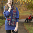 Unhappy Teenage Girl Standing In Autumn Park With Couple On Benc - Stock Photo