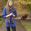 Unhappy Teenage Girl Standing In Autumn Park With Couple On Benc — Stock Photo