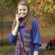 Teenage Girl On Mobile Phone In Autumn Park With Couple On Bench — Stock Photo