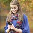 Teenage Girl Making Mobile Phone Call In Autumn Landscape — Stock Photo