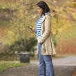 Teenage Girl Making Mobile Phone Call In Autumn Landscape — Stockfoto