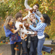 Group Of Teenage Friends Throwing Leaves In Autumn Landscape — Stock Photo