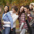 Stock Photo: Group Of Six Teenage Friends Having Fun In Autumn Park