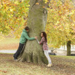 Foto Stock: Romantic Teenage Couple By Tree In Autumn Park