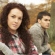 Foto Stock: Close Up Of Teenage Couple Sitting On Bench In Autumn Park