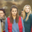 Teenage Girl Surrounded By Friends In Outdoor Autumn Landscape — Stock Photo