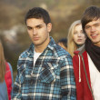 Teenage Boy Surrounded By Friends In Outdoor Autumn Landscape — Stock Photo
