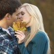 Romantic Teenage Couple Kissing Behind Autumn Leaf - Stock Photo