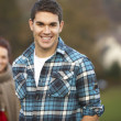 Foto Stock: Teenage Boy Outside With Girlfriend In Background