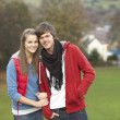 Romantic Teenage Couple Walking Through Autumn Landscape — ストック写真