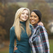 Foto Stock: Two Female Teenage Friends On Walk In Autumn Landscape
