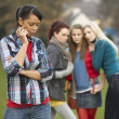 Upset Teenage Girl With Friends Gossiping In Background — Stock Photo #4837149
