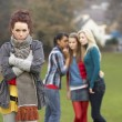 Upset Teenage Girl With Friends Gossiping In Background — Photo