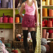 Young Woman Holding Knitted Scarf Standing In Front Of Yarn Disp — Stok fotoğraf