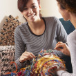 Two Women Knitting Together At Home - Stock Photo