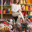 Woman Sitting On Stool Holding Knitting Needles In Front Of Yarn - Stock Photo