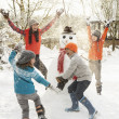 Mother And Children Building Snowman In Garden - Foto Stock