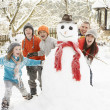 Family Building Snowman In Garden - Stock Photo