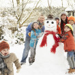 Family Building Snowman In Garden - Foto Stock