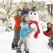 Family Building Snowman In Garden — 图库照片
