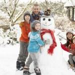 Family Building Snowman In Garden — Stock Photo