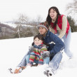 Family In Snow Riding On Sledge - Stockfoto