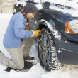 Man Putting Snow Chains Onto Tyre Of Car - Zdjcie stockowe