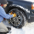 Man Putting Snow Chains Onto Tyre Of Car - Stok fotoğraf