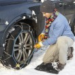 Man Putting Snow Chains Onto Tyre Of Car - Stock Photo