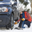 Woman Putting Snow Chains Onto Tyre Of Car - 图库照片