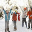 Children Building Snowman In Garden - 图库照片
