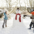Mother And Children Building Snowman In Garden - 图库照片