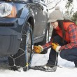 Woman Putting Snow Chains Onto Tyre Of Car - Zdjcie stockowe