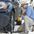Man Putting Snow Chains Onto Tyre Of Car - Lizenzfreies Foto