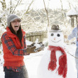 Стоковое фото: Young Couple Having Snowball Fight In Garden