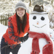 Young Woman Building Snowman In Garden - 图库照片