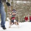 Father Pulling Children On Sledge Through Winter Landscape - 图库照片